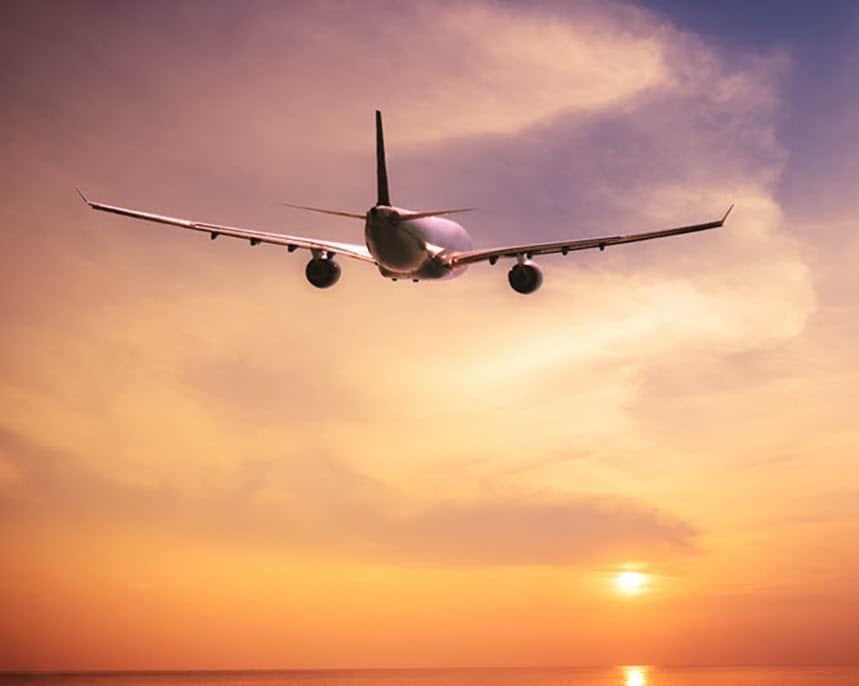 aeroplane flying into the sunset