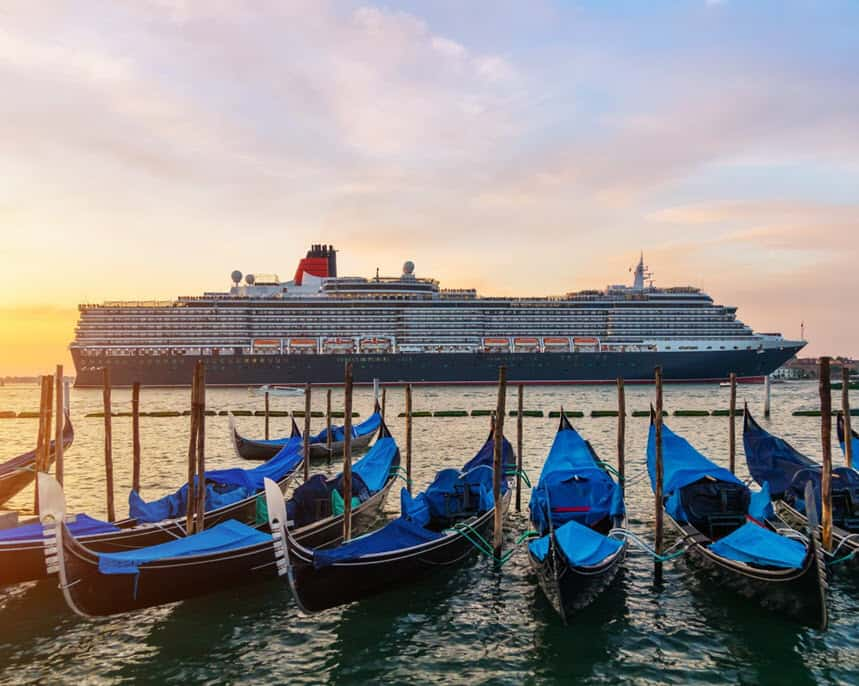row of gondolas in Venice with cruise ship in the background